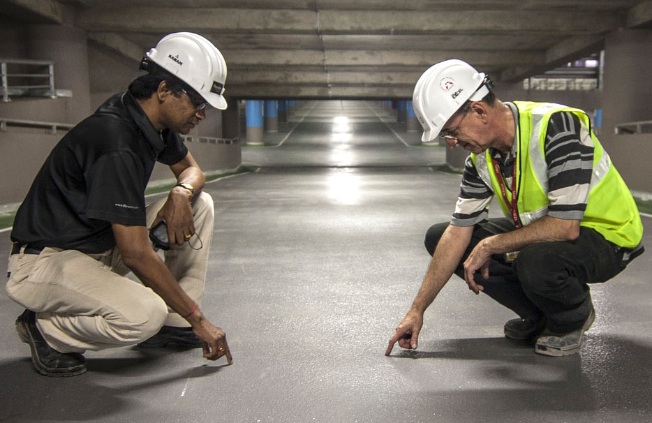 Construction workers examine a concrete road.